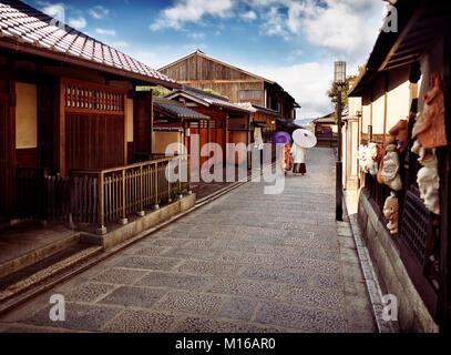 Paar mit japanischen Sonnenschirme in traditioneller Kimono hinunter eine alte Straße Yasaka Dori, Kyoto, Kyoto, - Stockfoto
