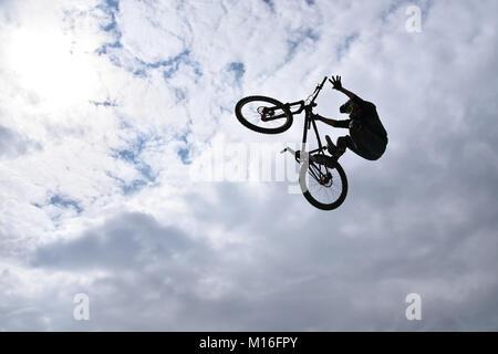 Die Silhouette eines jungen Mannes freestyle stunt Radfahrer in den Himmel darstellenden Stunt springen von einem - Stockfoto