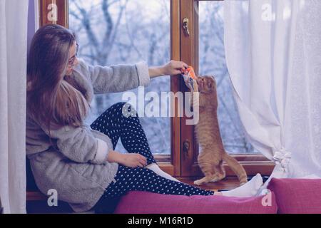 Schöne Mädchen in Gläsern sitzt auf der Fensterbank. Sie spielt mit ein wenig Ingwer Kätzchen. Er fängt das Spielzeug - Stockfoto
