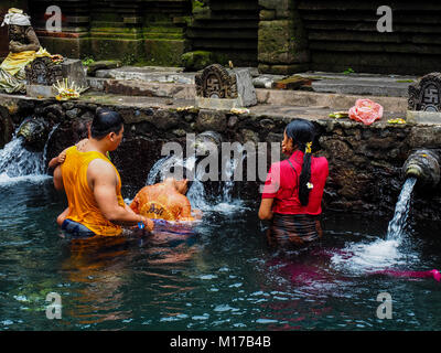 Balinesische Familie beten und Baden im Pura Tirta Empul - ein Hindu berühmten Tempel in Bali. - Stockfoto