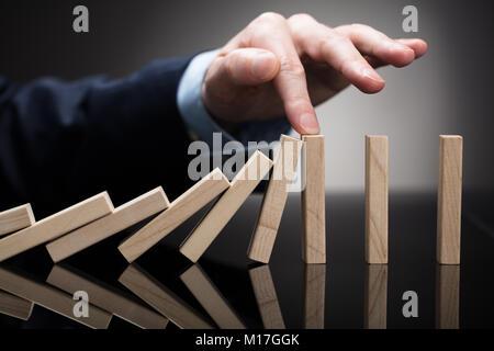 Nahaufnahme einer Businessperson stoppen Holzblöcke mit seinem Finger auf Schreibtisch - Stockfoto