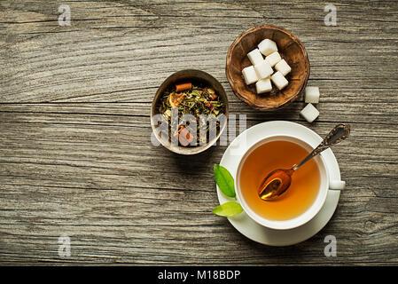 Tasse Tee mit trockenen Grüner Tee mit Zucker auf hölzernen Tisch - Stockfoto