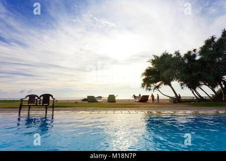 Ahungalla, Sri Lanka - Dezember 2015 - ein Hotel Pool Blick auf Silhouetten zu Fuß in Richtung Strand bei Sonnenuntergang - Stockfoto