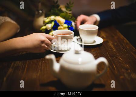 Weiße Tassen in die Hände mit einer geringen Tiefenschärfe - Stockfoto