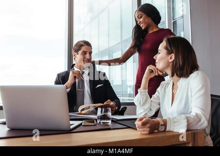 Drei Personen im Tagungsraum diskutieren neue Business Plan. Unternehmer im Gespräch mit weiblichen Kollegen im - Stockfoto