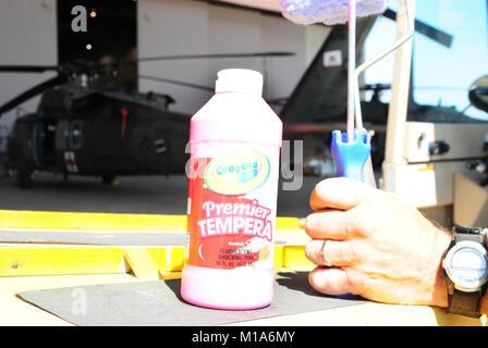 Eine Flasche fluoreszierenden Rosa tempera Farbe ist über auf einem Kalifornien Army National Guard UH-60 Black - Stockfoto