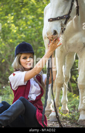Schöne Frau auf dem Boden mit braunen Pferd neben ihr sitzen. - Stockfoto