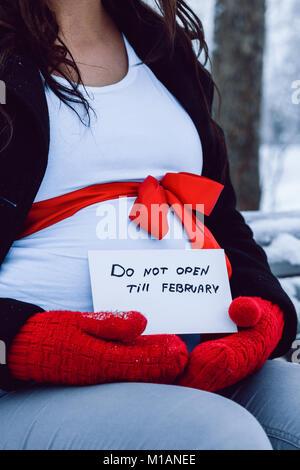 Stadt Cesis, Winter, Dezember, Lettland, Schwangere Frau warten brennen Mädchen, Natur und Schnee. Rote Handschuhe. - Stockfoto