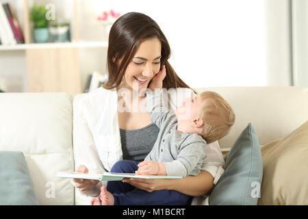 Mutter und Sohn, die einander mit Buch auf einer Couch im Wohnzimmer zu Hause sitzen - Stockfoto