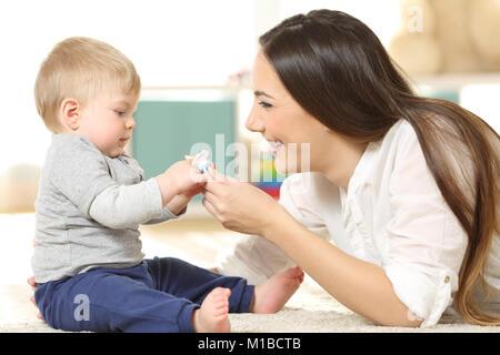 Seitenansicht Porträt eines stolzen Mutter geben einen Schnuller, um Ihr Baby auf dem Boden zu Hause - Stockfoto