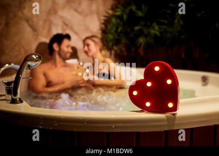 Herz auf dem Hintergrund ein romantisches Paar mit Champagner in der - Stockfoto