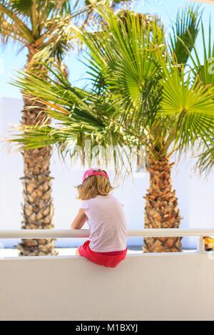 Mädchen mit Brise im Haar, sitzen auf den weißen Zaun mit Blick auf die traumhaften tropischen Meer zwischen zwei - Stockfoto