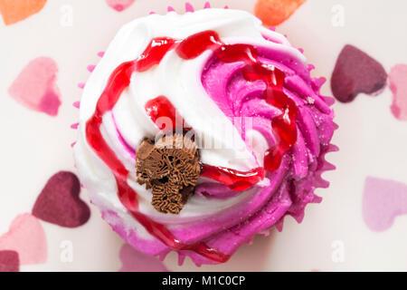 Raspberry Ripple Cupcake mit Schokolade flake auf Herzen Platte - von oben nach unten suchen. - Stockfoto