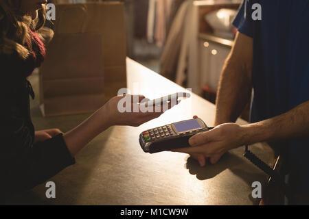 Frau, die Zahlung über Mobiltelefon - Stockfoto