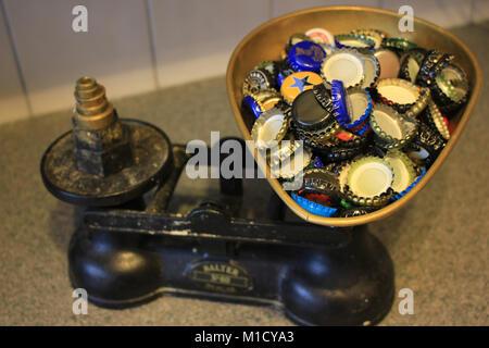 Bier Flasche Oberseiten wurden gesammelt und werden auf eine altmodische Waage gewogen. - Stockfoto