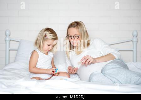 Schwangere Mutter morgens spielend mit ihrer Tochter im Bett - Stockfoto