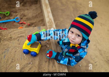 Sehr ernsten Kind mit Spielzeug spielen und Spaß haben in der Sandbox. Schöne Kind spielt auf dem Spielplatz mit - Stockfoto