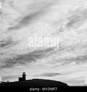 Paar neben Belle Tout Lighthouse, Beachy Head, East Sussex, gegen grosse Himmel mit Wolken Silhouette - Stockfoto