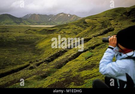 Island. Landmannalaugar Nationalpark. Wanderer, Frau, sieht durch ein Fernglas in der Landschaft. - Stockfoto