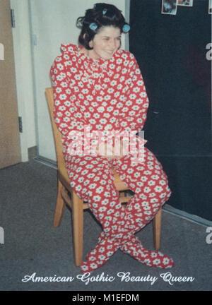 Teenager mit Rollen in ihrem Haar zu tragen One-Piece Footed Pajamas, USA - Stockfoto