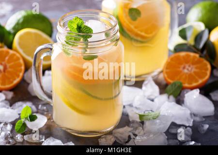 Citrus Limonade mit Scheiben von Orangen, Zitronen und Limetten in Maurergläser Stockfoto