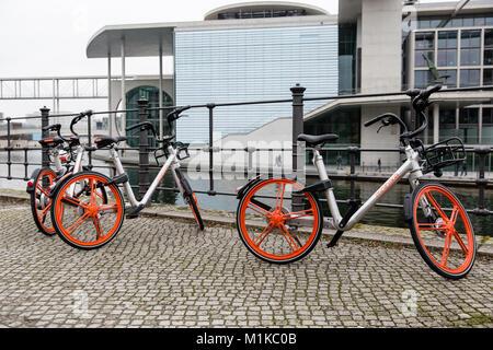 Parken Öffentliche Fahrräder mobike auf der Straße mit pflastersteine entlang der Spree im Stadtzentrum von Berlin - Stockfoto