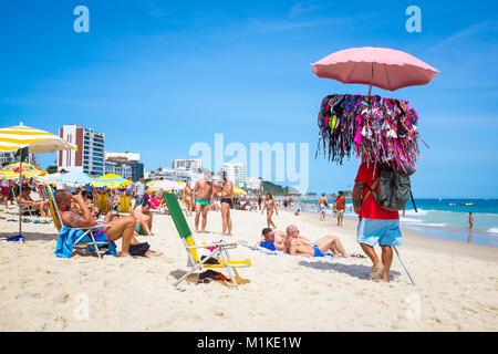 RIO DE JANEIRO - 5. Februar 2017: Ein Strand Anbieter verkaufen Bikinis Pässe Beachgoers genießen einen heißen Sommertag - Stockfoto
