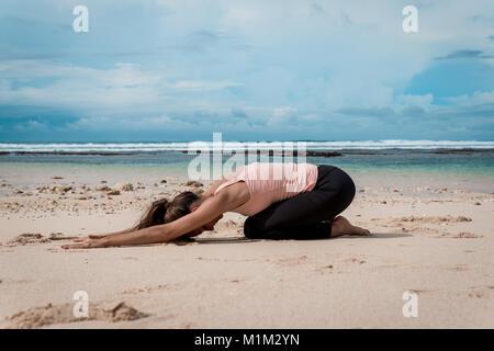 Praktizierende Frau Yoga am Strand - embryostellung - Stockfoto