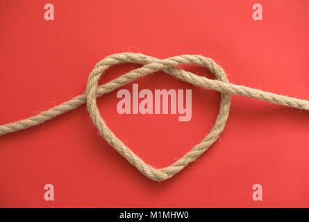 Die Form eines Herzens von einem Seil auf rotem Hintergrund - Stockfoto