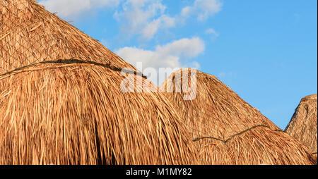 Stroh Sonnenschirme/Bambus Sonnenschirme gegen den blauen Himmel Hintergrund. - Stockfoto