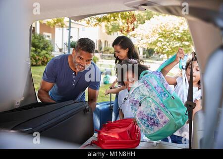 Familie verlassen für Ferienhäuser Laden das Gepäck ins Auto - Stockfoto