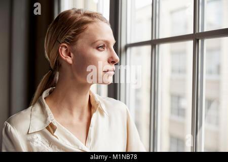 Blonde junge geschäftsfrau Blick aus Fenster - Stockfoto