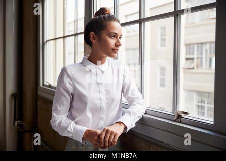 Junge Frau mit Haar bun Blick aus Fenster, Taille bis - Stockfoto