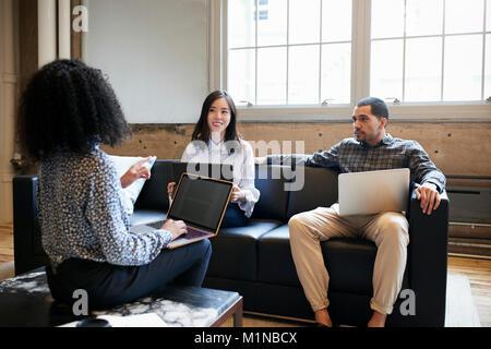 Drei junge Kolleginnen und Kollegen mit Laptops auf eine lockere Treffen