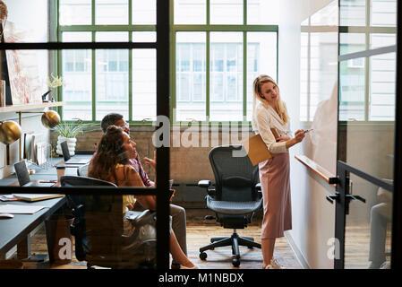 Frau am Whiteboard in Teammeetings, durch offene Tür gesehen - Stockfoto