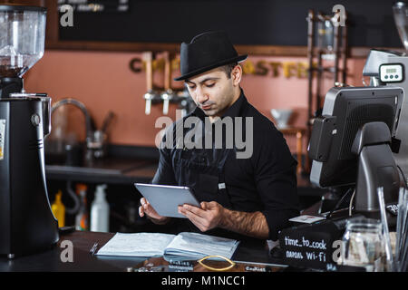 Portrait von barista Holding digital Tablet am Zähler im Coffee Shop. - Stockfoto