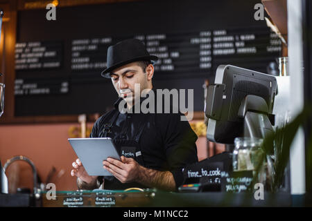 Portrait von barista Holding digital Tablet am Zähler im Coffee Shop. - Stockfoto