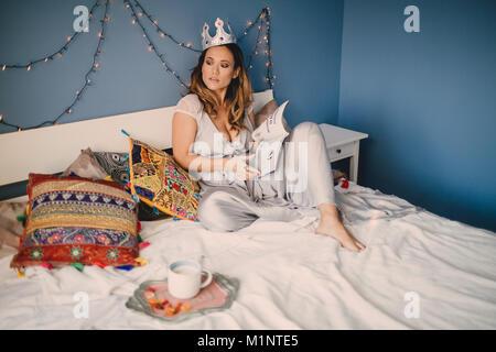 Das Mädchen mit der Krone auf dem Bett liegend im Haus, - Stockfoto
