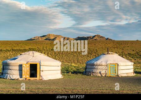 Zwei mongolische Nomaden Gers und Bergen im Hintergrund, Bayandalai Bezirk, Provinz im Süden der Wüste Gobi, Mongolei, - Stockfoto