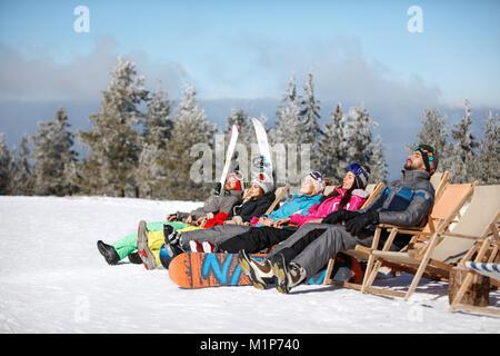 Männliche und weibliche Skifahrer Sonnenbad im Solarium auf Gelände - Stockfoto