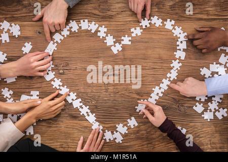 Hohe Betrachtungswinkel aus Geschäftsleuten, die Herzform Schild mit Puzzle - Stockfoto