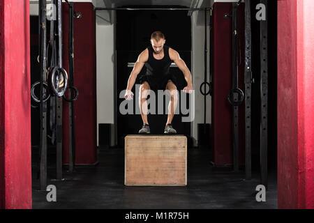 Junge Athlet Mann tut einem Kasten springen Übung In der Turnhalle - Stockfoto