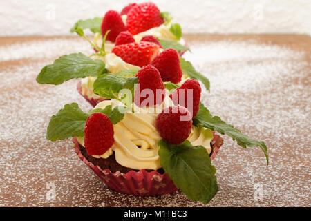 Hausgemachte leckere Schokolade Cupcakes mit frischen Himbeeren und Sahne. Lecker Kuchen für Valentinstag. - Stockfoto