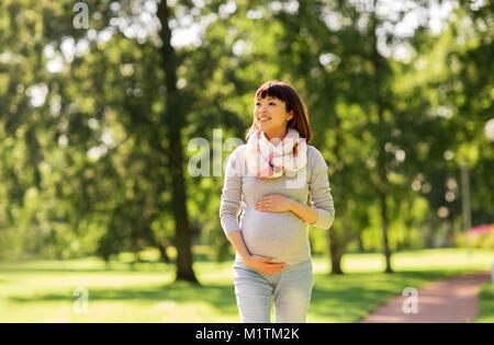 Glücklich schwanger asiatische Frau Wandern im Park - Stockfoto