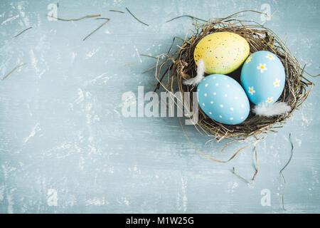 Ostereier im Nest auf Blau Holz- Hintergrund. Verzierten Ostereier mit Federn im Nest auf dem alten Holztisch mit - Stockfoto