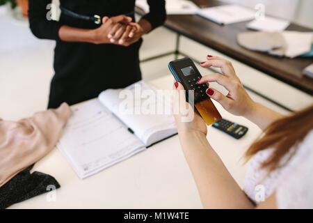 Kunden shopping Designer Verschleiß an eine Modeboutique. 7/8 Schuß des Kunden die Zahlung durch Eingabe Ihrer PIN - Stockfoto