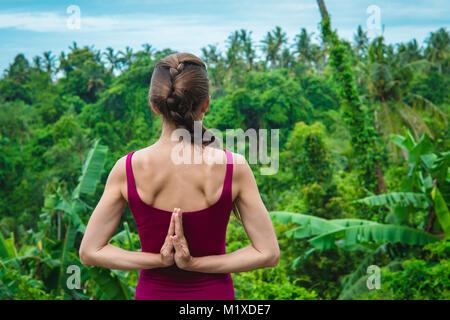 Junge Frau Yoga mit Namaste hinter dem Rücken - Stockfoto