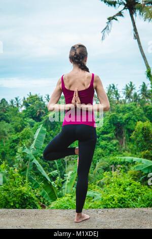 Junge Frau Yoga tree Pose mit Namaste hinter dem Rücken - Stockfoto