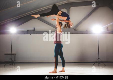 Das Thema der Acroyoga und Yoga Posen. Ein Paar aus zwei Männer und eine Frau stehen in der Position der Asana. - Stockfoto