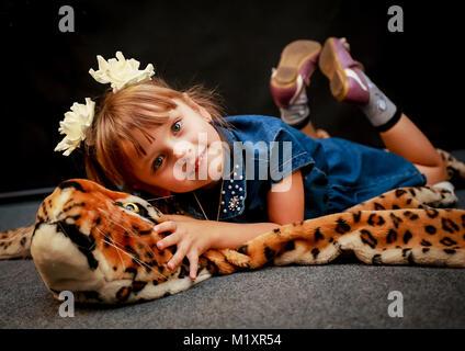 Auf einem schwarzen Hintergrund auf der Haut eines Spielzeugs leopard liegt der Frauen Baby und lächelnd - Stockfoto